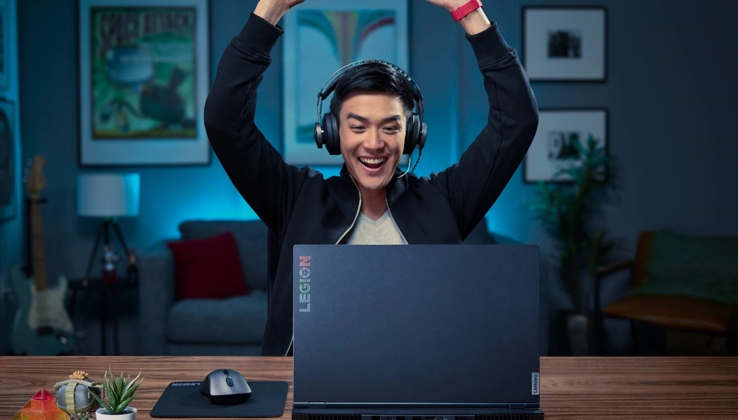 Gammer with headphones celebrate his win in front of a Laptop